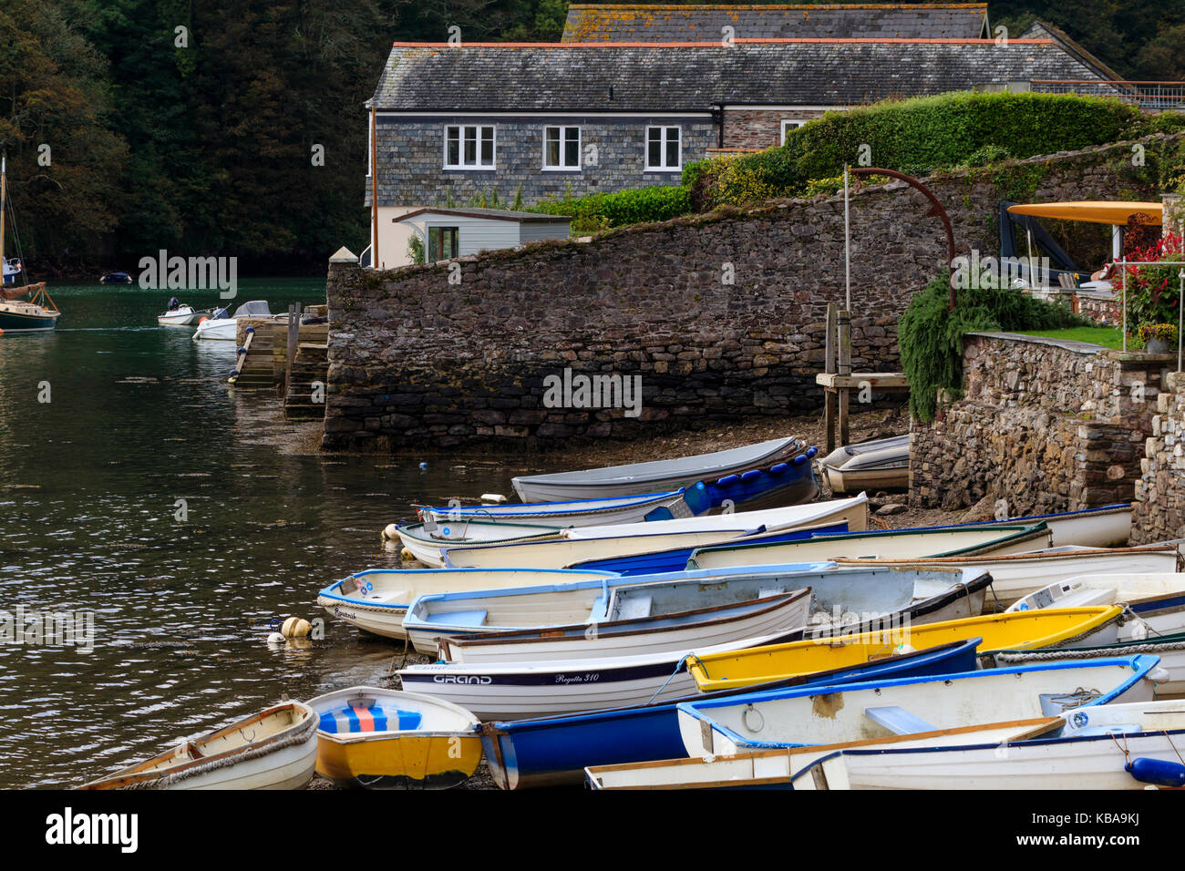 Beached dinghies tied up on the tidal shoreline of the River Yealm at Newton Ferrers, Devon, UK - Stock Image