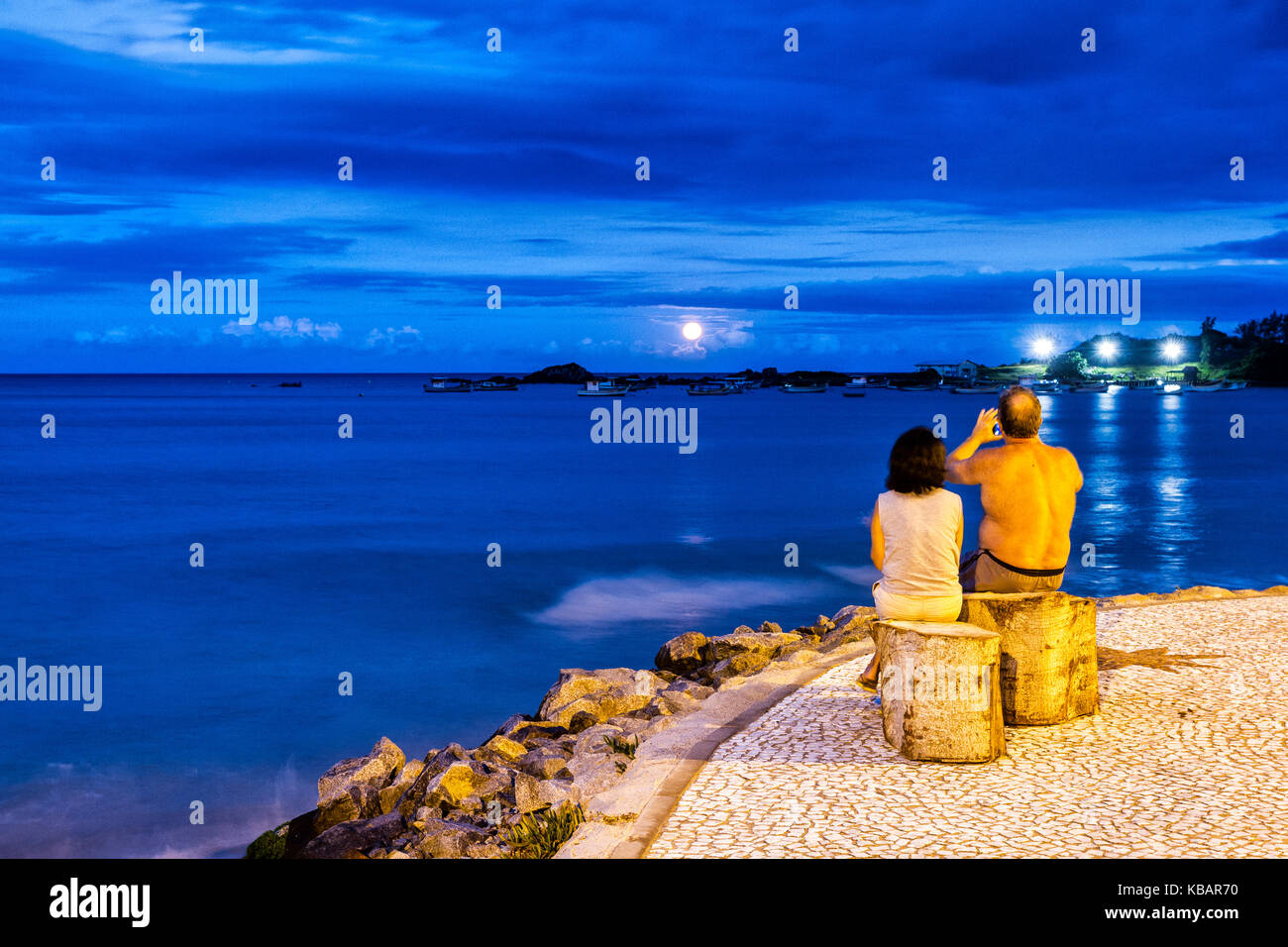 Mature couple watching full moon rising at Armacao Beach at dusk. Florianopolis, Santa Catarina, Brazil. - Stock Image