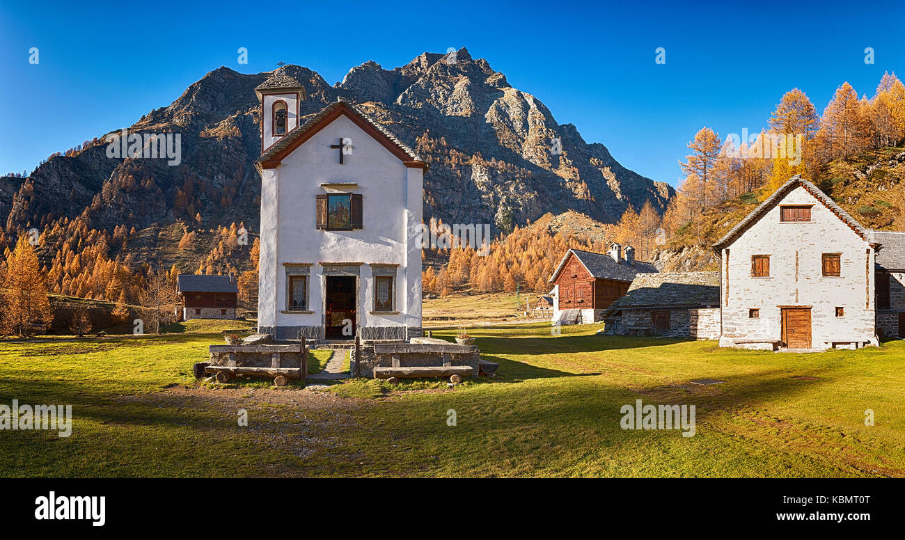 Small church in ancient village at sunset in autumn season with long shadow on the green grass - Stock Image
