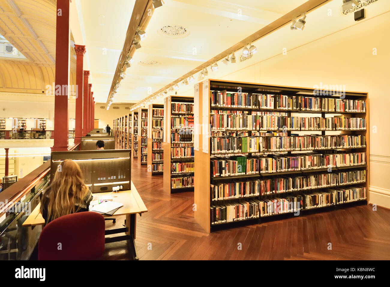 Australia Melbourne: State Library of Victoria. Visitor studying at reading desk beside rows of book shelves. - Stock Image