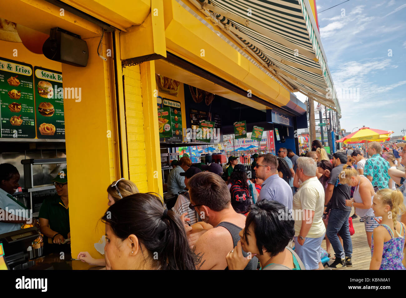 Line of visitors and tourists at Nathan's Famous restaurant on the Coney Island boardwalk. - Stock Image
