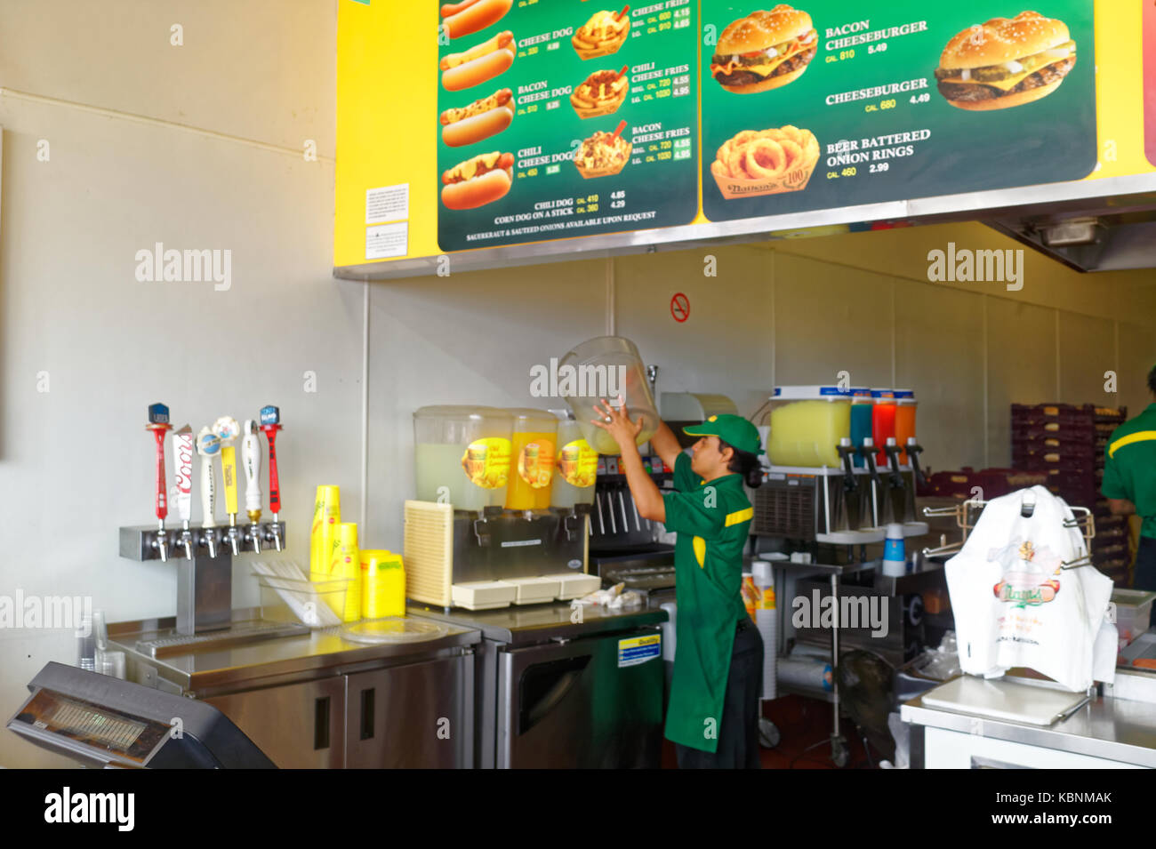 Worker's behind the counter at Nathan's Famous hot dog restaurant with the large menu board. - Stock Image