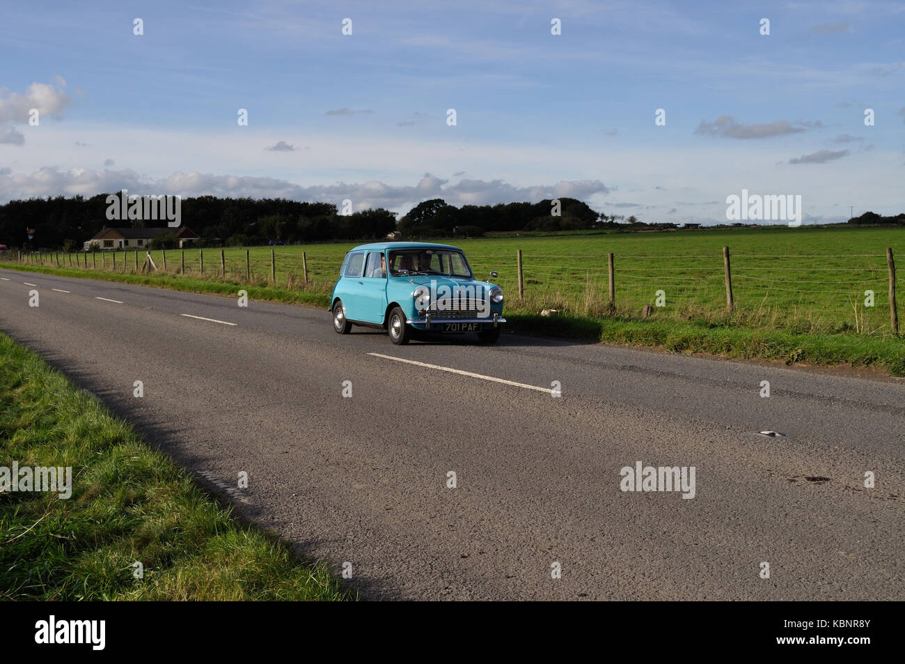A blue Austin Mini leaves the Winkleigh site of the West of England Transport Collection Open Day on 6th October - Stock Image