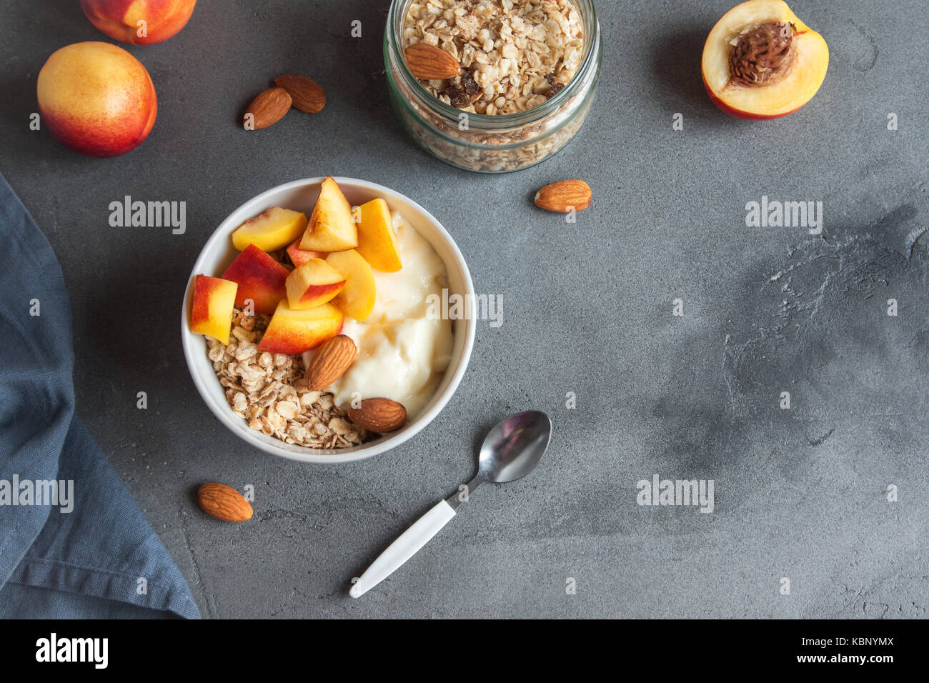 Homemade oatmeal granola with yogurt and peaches in bowl for healthy breakfast. Cereal and fruit breakfast bowl - Stock Image