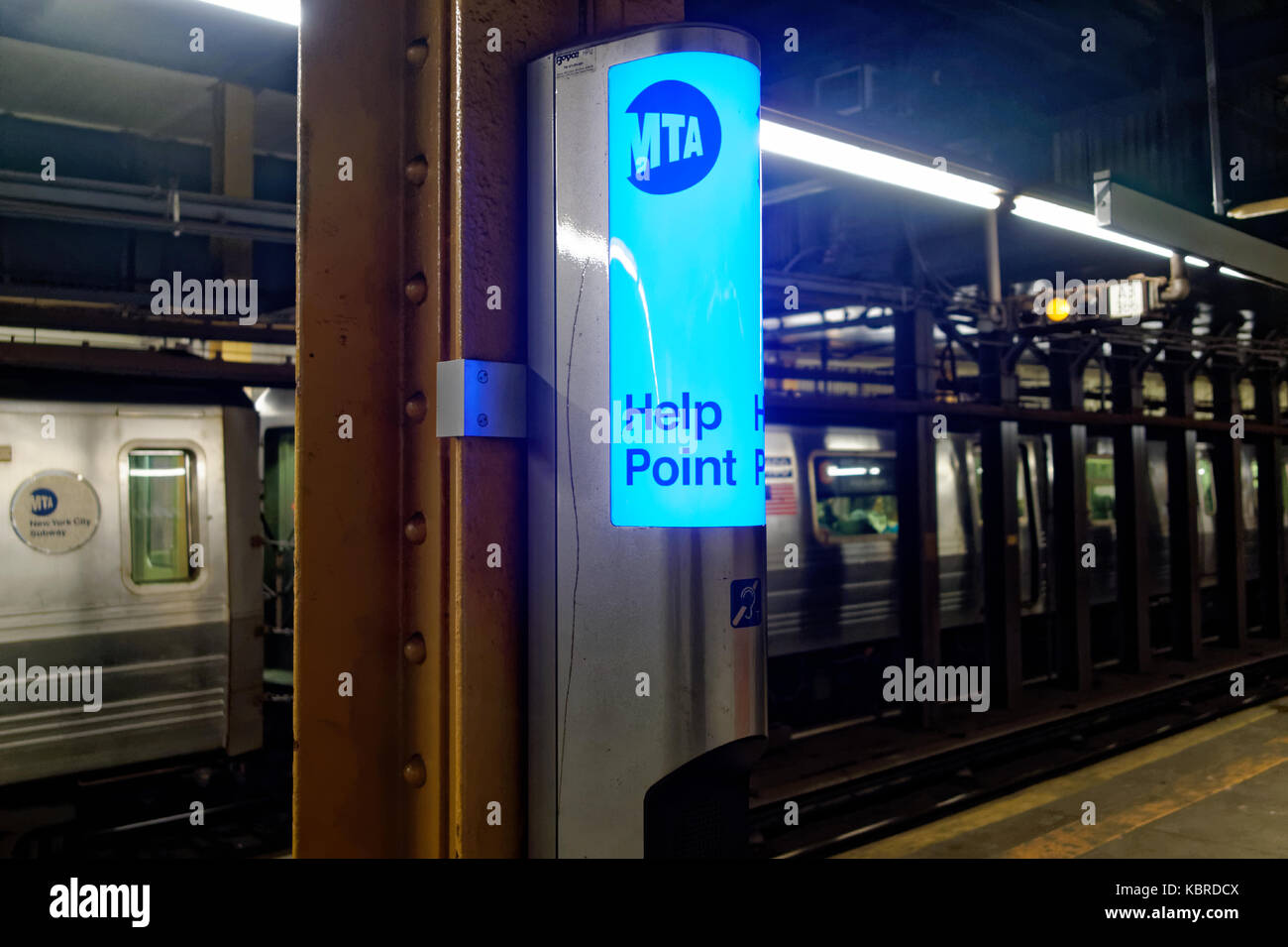 MTA emergency telephone or intercom on a subway platform with train arriving in the background. - Stock Image