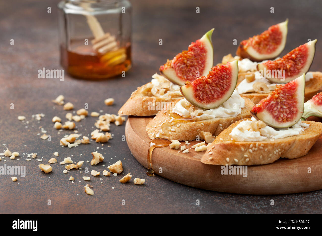 sandwiches with figs, ricotta, honey and walnuts on a brown background - Stock Image