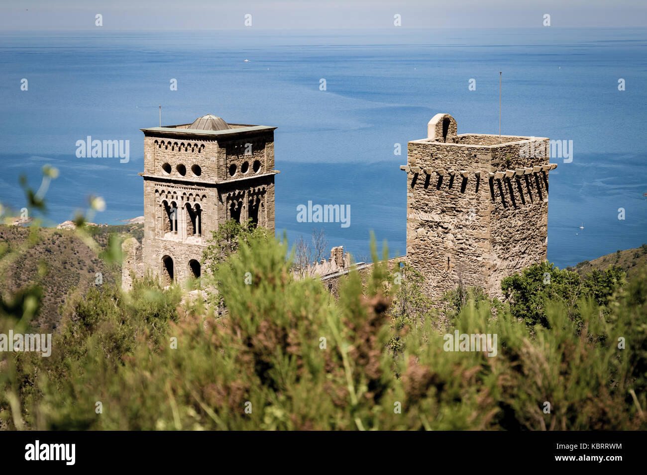 Bushes on the foreground and monastery of Sant Pere de Rodes in back - Stock Image
