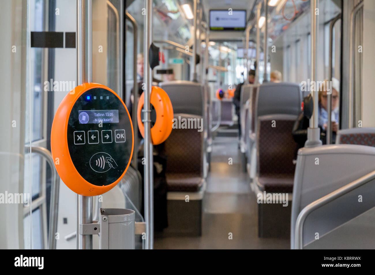 Orange modern magnetic ticket validator with tram and people in background - Stock Image