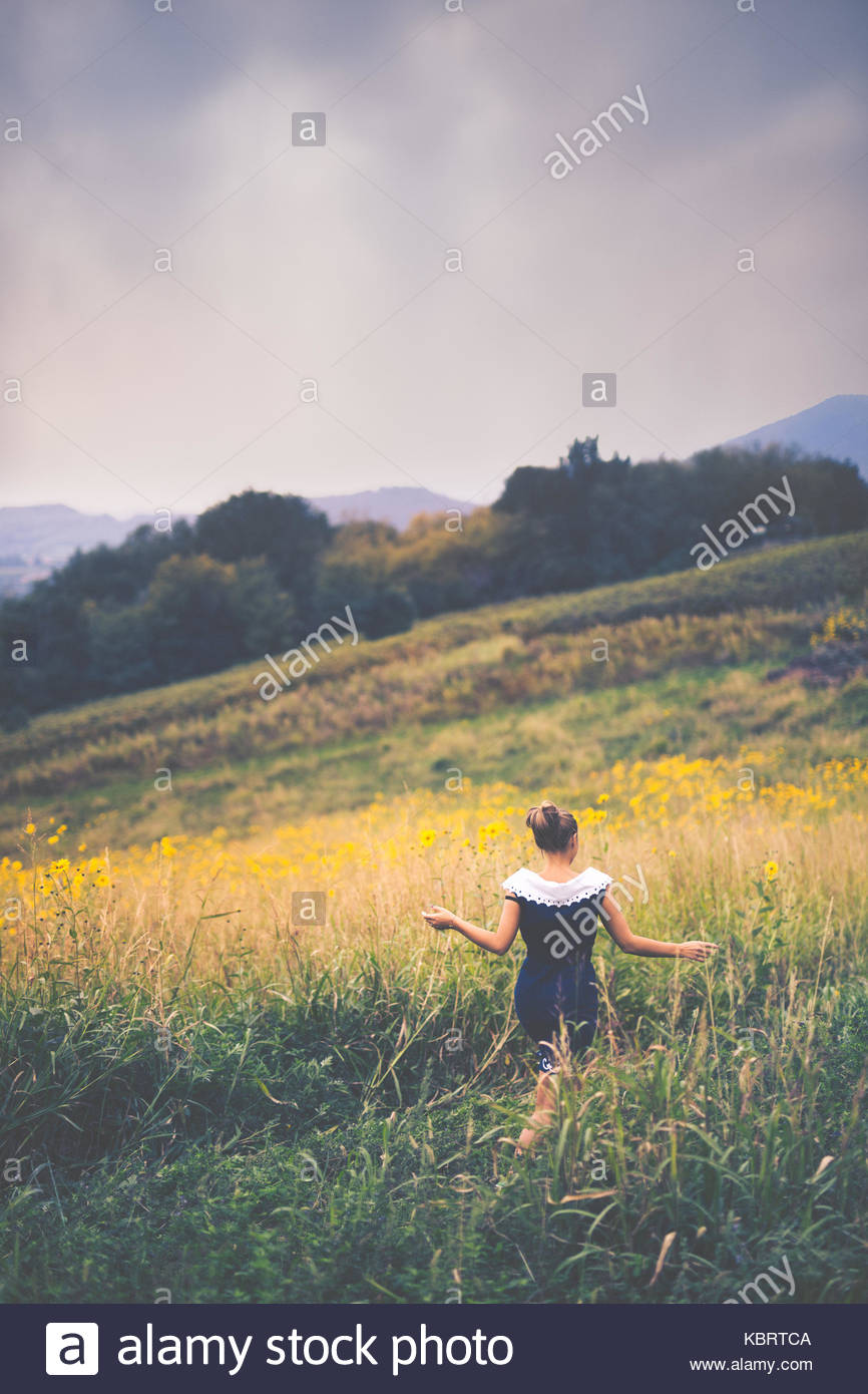 Girl carelessly running in a field in the countryside - Stock Image