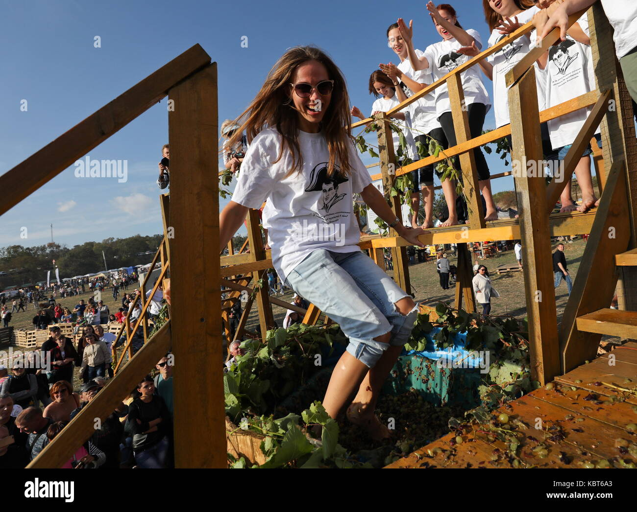 Crimea, Russia. 30th Sep, 2017. A girl stomps grapes at the WineFest grape harvesting and wine making festival at Stock Photo