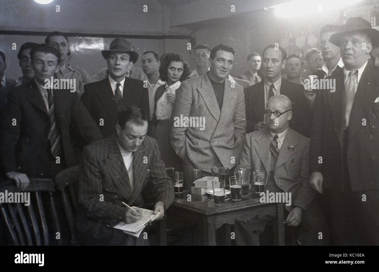1950s, historical, group of people, mainly men, journalists for a local newspaper, enjoying a drink while viewing - Stock Image