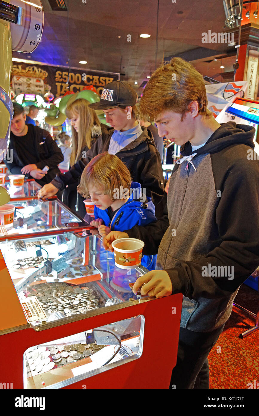 young children and teenagers playing gambling games in an amusement arcade on the golden mile, blackpool, england, - Stock Image