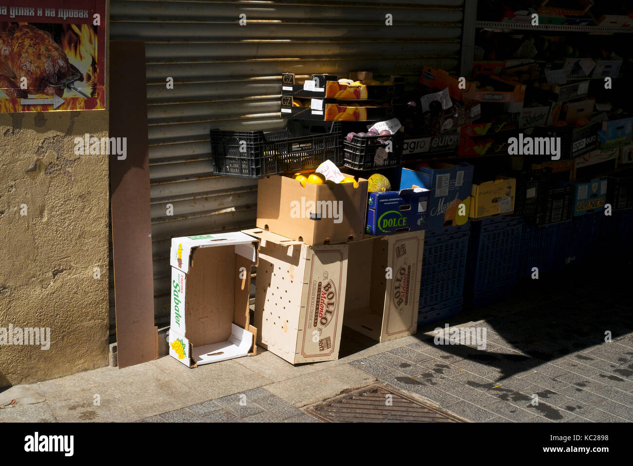 Fruit and vegetables stacked up in boxes and pallets in a side street of Lloret de Mar, Spain - Stock Image
