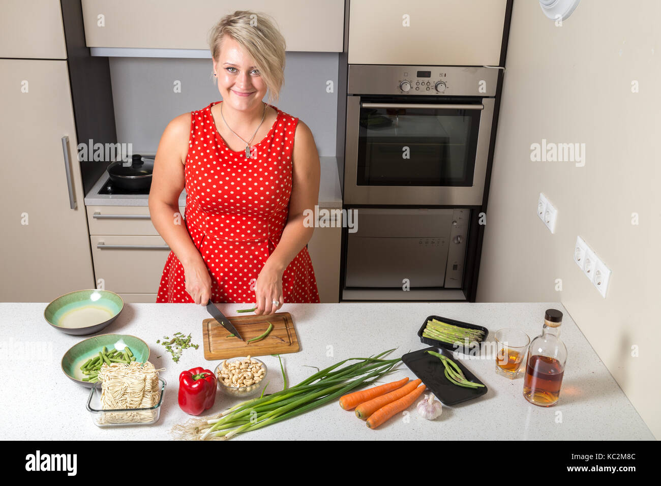 Girl smiling and cutting asparagus - Stock Image