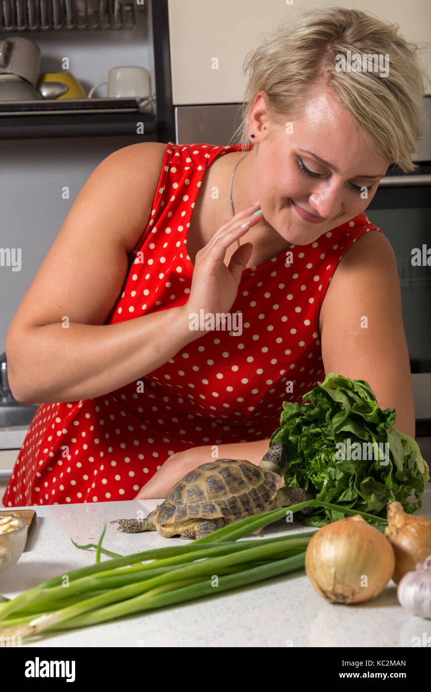Girl smiles and observes tortoise who is eating - Stock Image