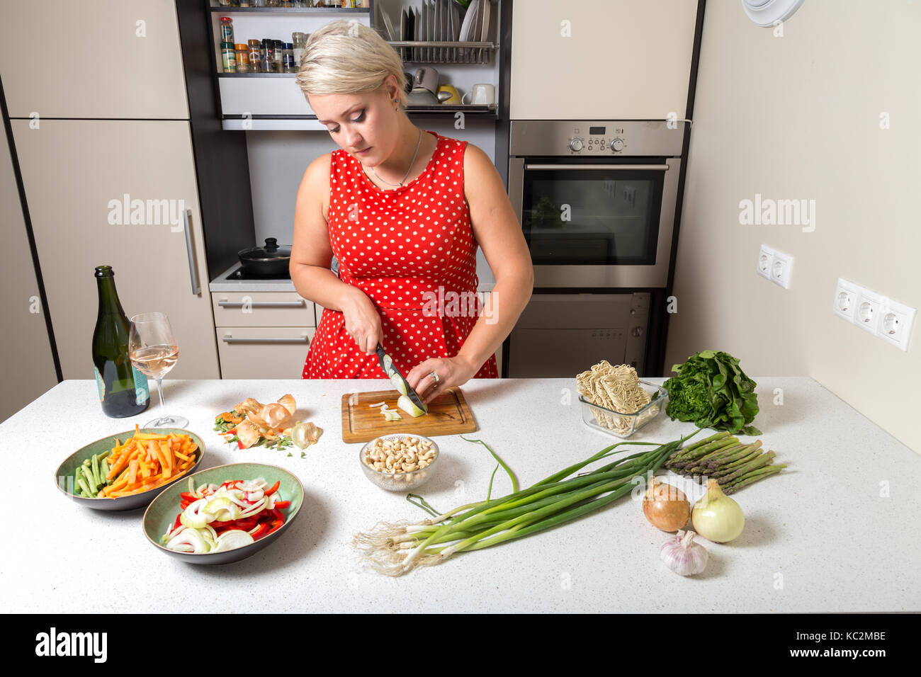 Girl cutting onions in red dotted dress - Stock Image