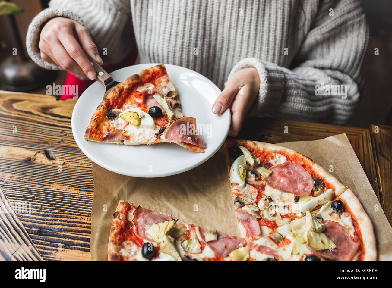 Woman hands put on a plate a piece of fresh hot pizza with ham, artichokes, olives and tomatoes - Stock Image
