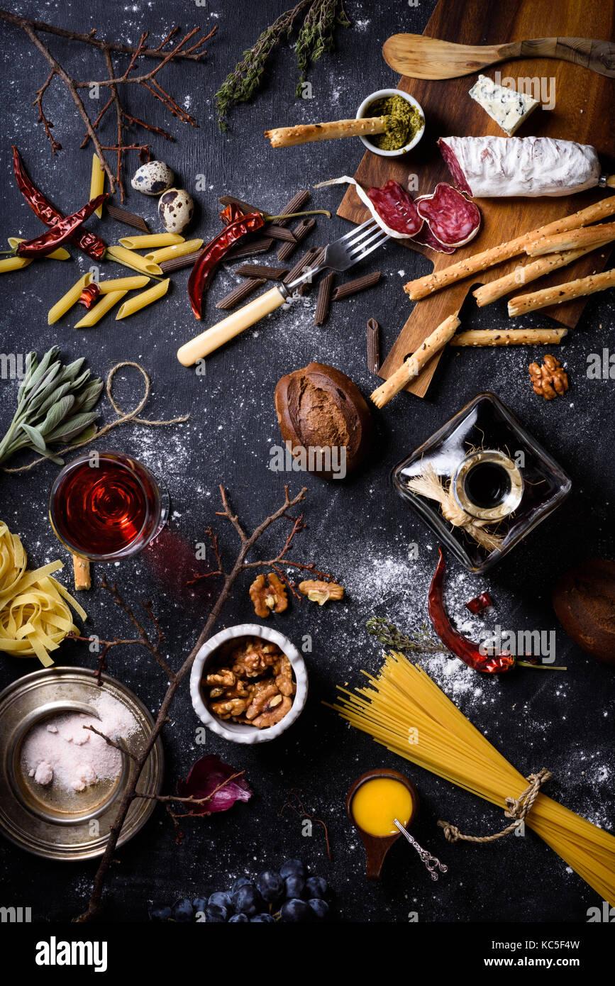 Appetizer, Italian kitchen ingredients. Pasta with antipasto,  cheese, grissini bread sticks,  spaghetti and wine - Stock Image