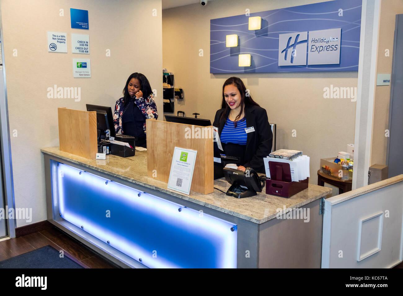 Silver Spring Maryland Holiday Inn Express hotel front desk registration Black woman clerk job lobby interior employee - Stock Image