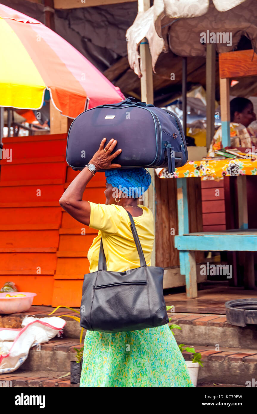 Woman at Grenadas St. George's market square  carries heavy bag on her head, Grenada and the Grenadines - Stock Image