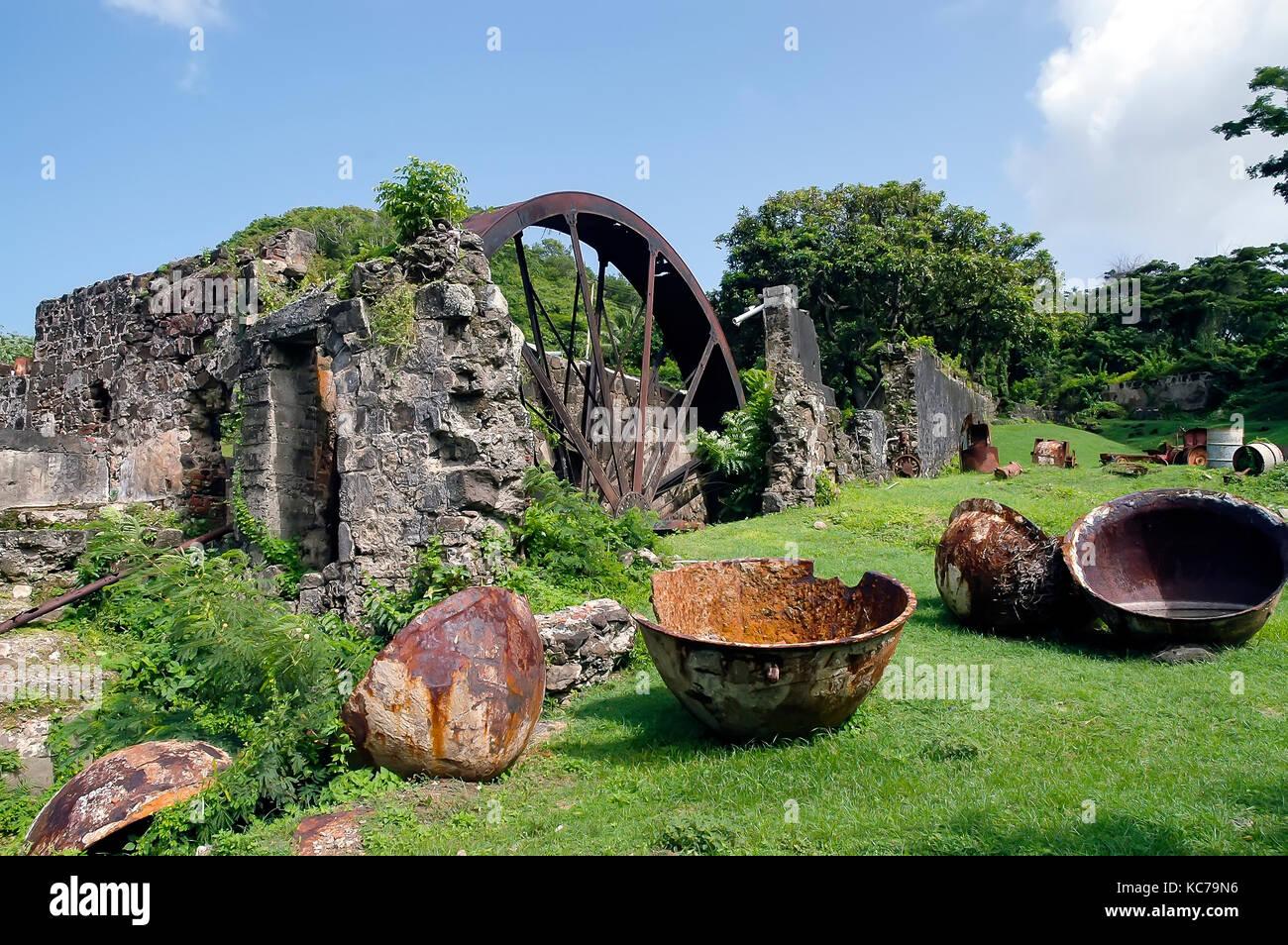 River Antoine Rum Distillery  old waterwheel and metal vats Grenada - Stock Image