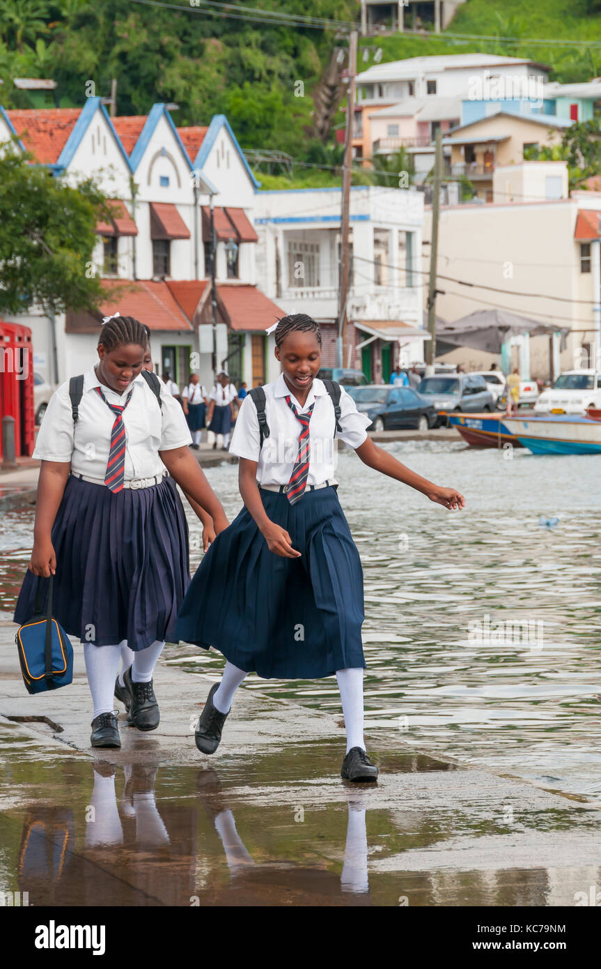 Two school girls in uniforms with neckties jump rain puddle at St. George's Carenage Grenada - Stock Image