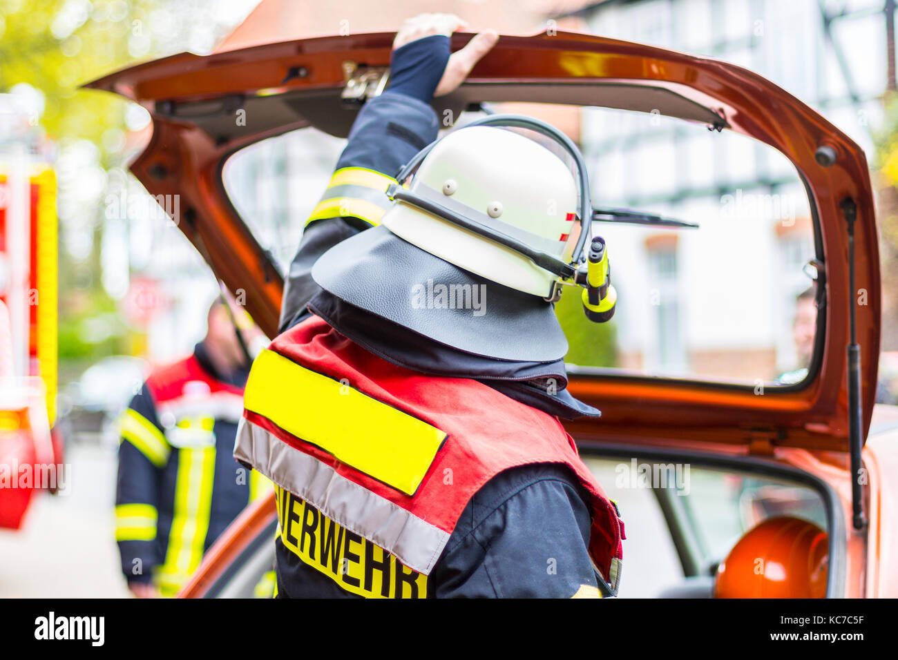 german fireman with helmet holds his hand on car bootlid - Stock Image