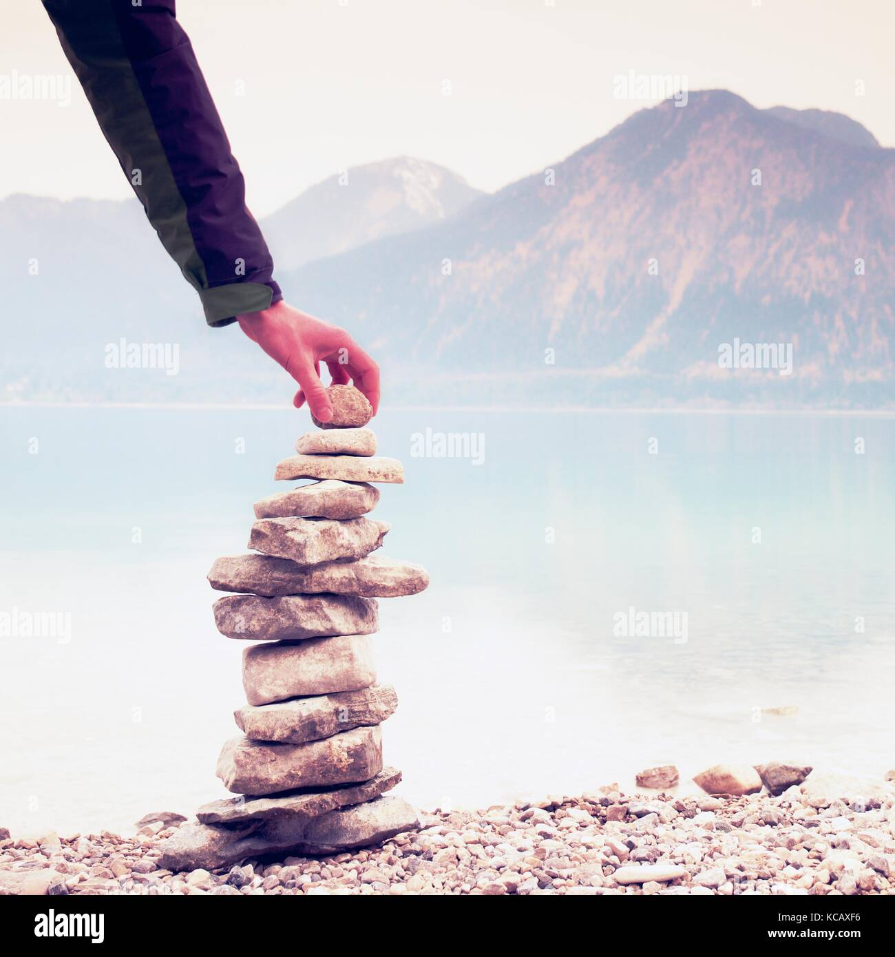 Man built pyramid from pebbles. Balanced stone pyramide on shore of blue water of mountain lake. Blue mountains - Stock Image