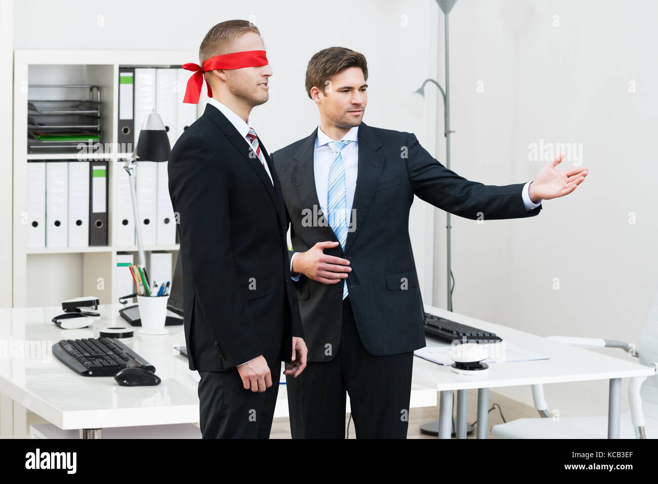 Confident Young Businessman Assisting Blindfolded Partner In Office - Stock Image