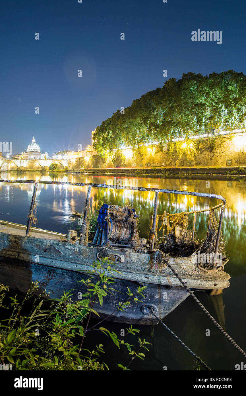 Beautiful night view of the Saint Peter Basilica. Photo taken on the banks of the Tiber River with an old boat in - Stock Image