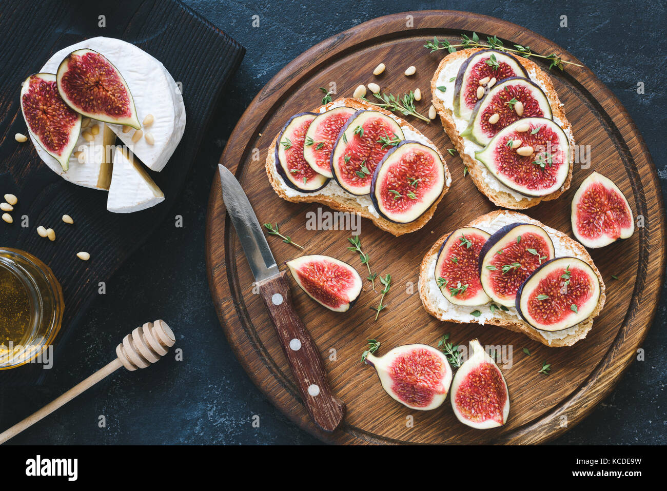 Bruschetta with fresh purple figs, ricotta cheese and honey on wooden cutting board served with brie camambert cheese - Stock Image