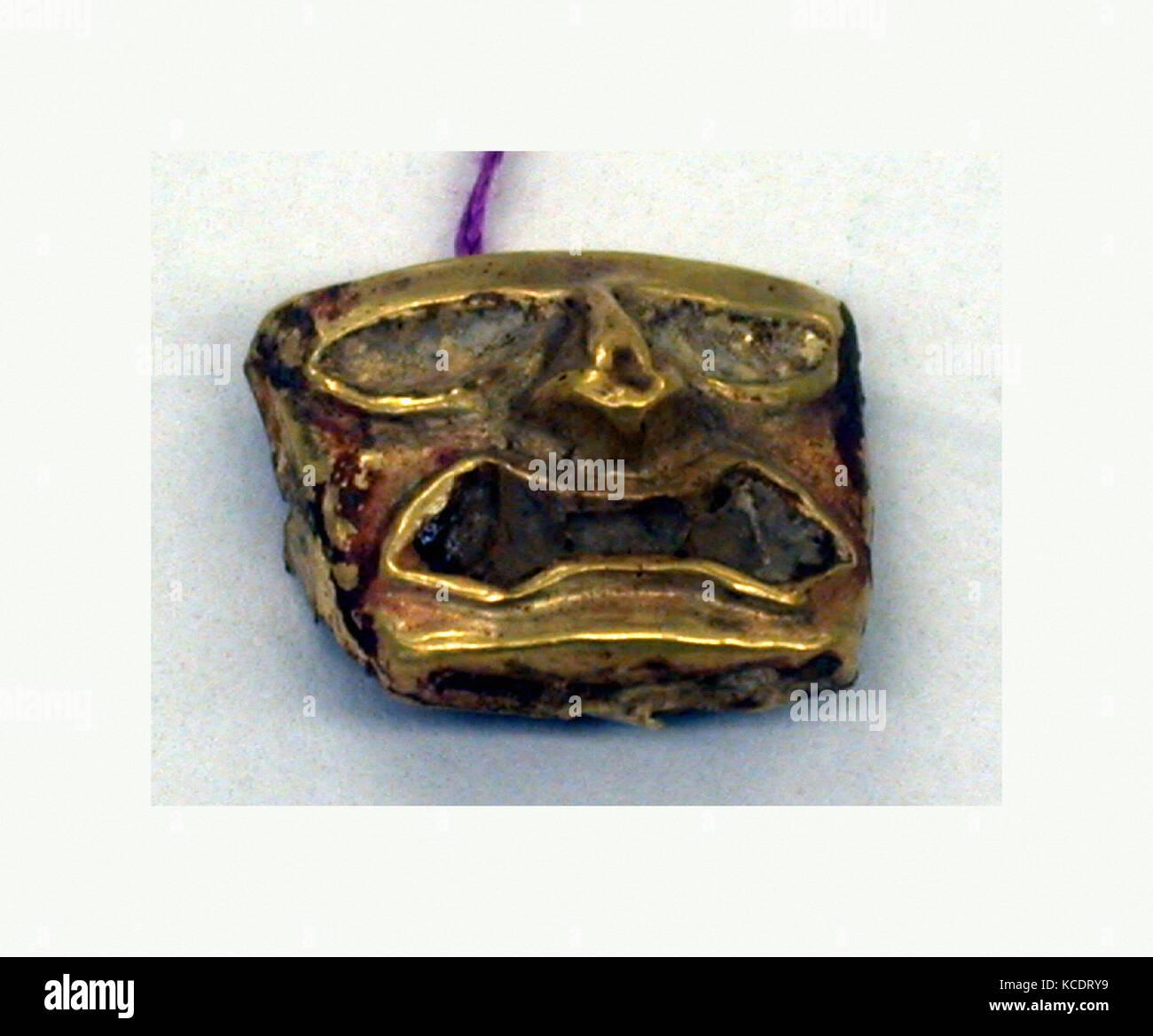 Gold Face Mask Ornament, 390–450, Peru, Moche (Loma Negra), Gold, H x W: 1/2 x 5/8in. (1.3 x 1.6cm), Metal-Ornaments - Stock Image
