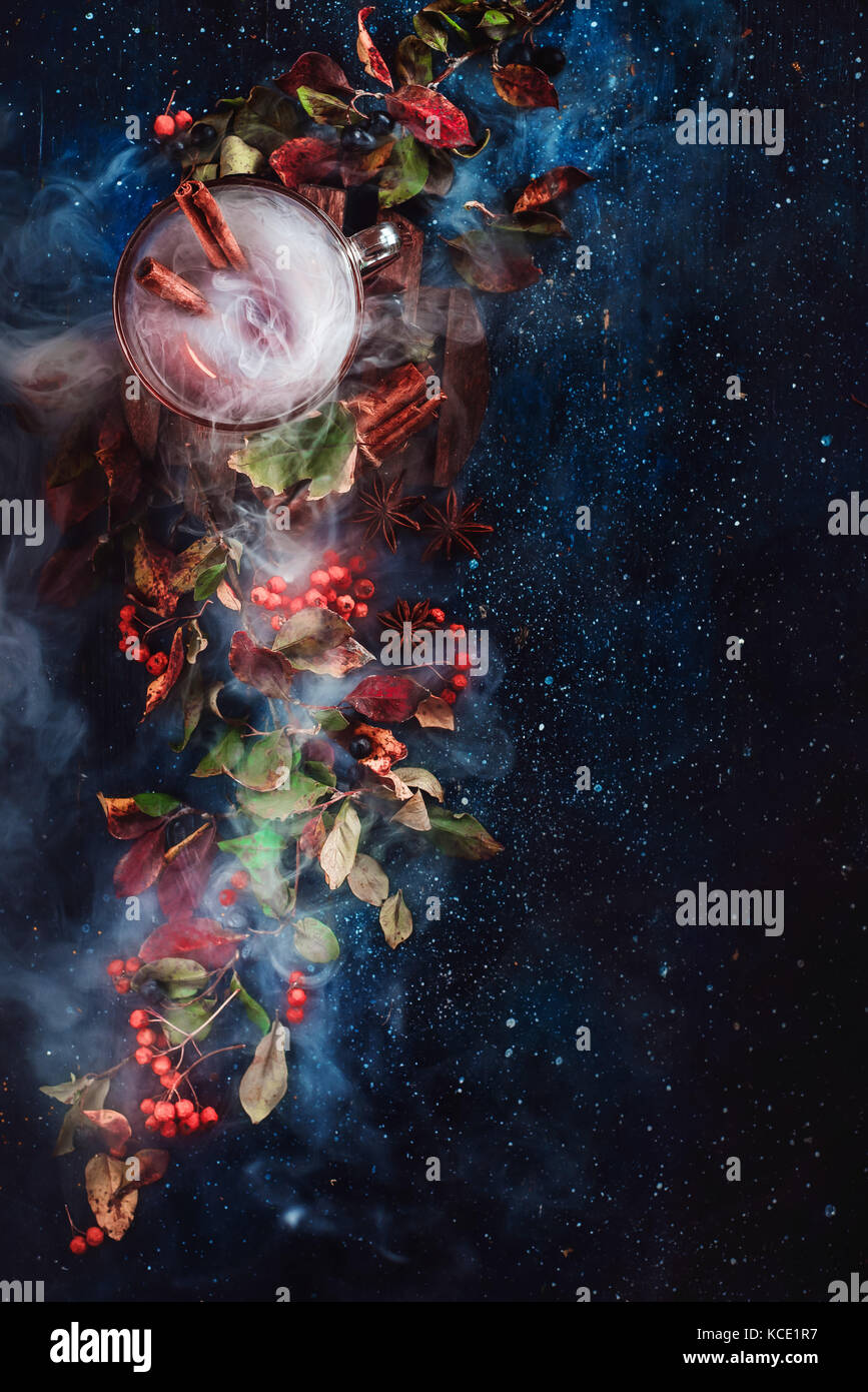 Steaming tea cup on a dark floral background with autumn leaves, berries, rowan, cinnamon and ingredients for autumn - Stock Image