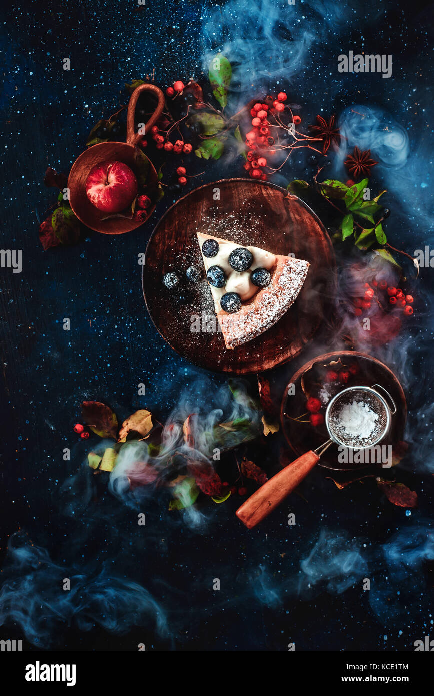A piece of cake with powdered sugar and a strainer on a dark wooden background with floral decoration. Handmade - Stock Image