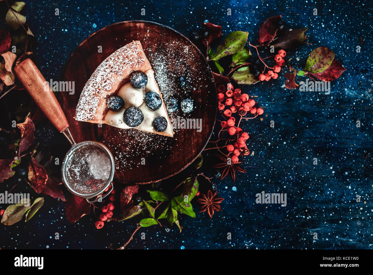 Close-up of a piece of pumpkin pie with powdered sugar and a strainer on a wooden plates. Handmade dishes in autumn - Stock Image