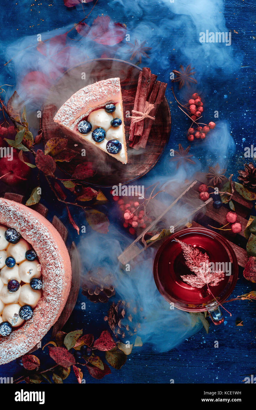 Dark autumn still life with a whipped cream blueberry cake, hot tea and floral decoration on a background with leaves - Stock Image