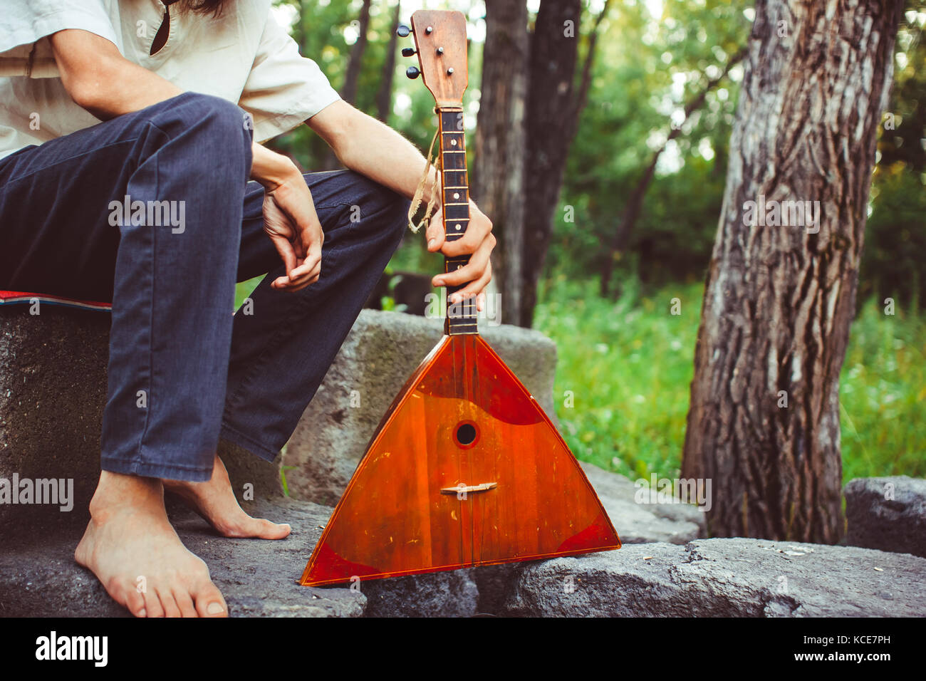 man holds in hands a balalaika in the woods - Stock Image