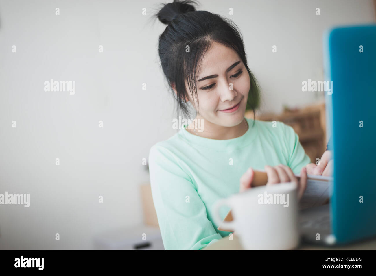 Young attractive Asian woman freelancer writing on notebook by left hand while working with laptop computer. Work - Stock Image