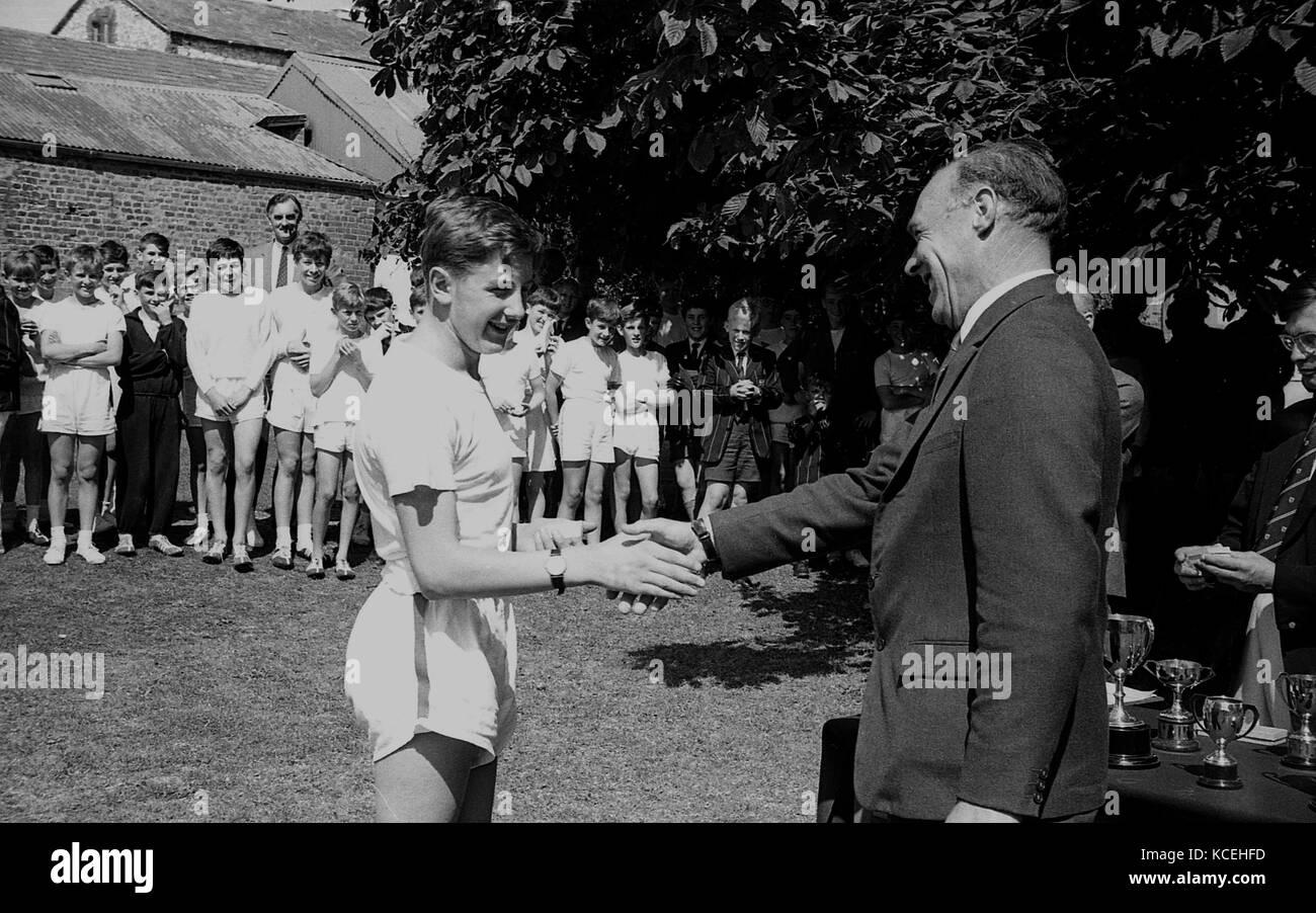1965, historical, a boy pupil at Thomas Hardye's boys School in Dorchester getting a congratulatory handshake - Stock Image