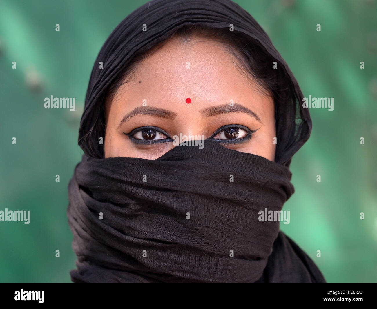 Full-face view of a young Assamese Hindu beauty with almond-shaped eyes, covering her hair and face with a secular, - Stock Image