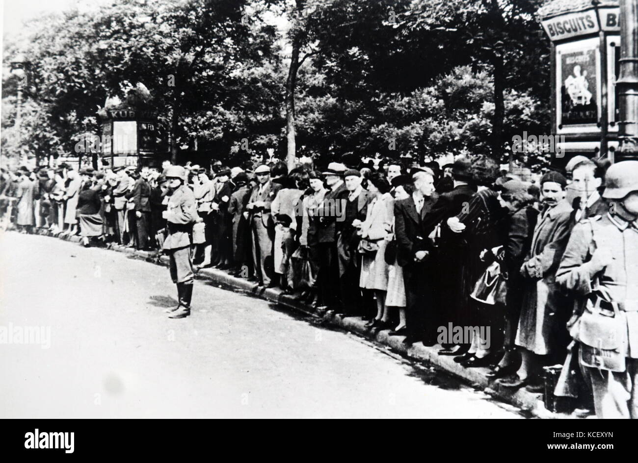 Photograph of crowds gather on the Champs-Élysées in Paris to see German troops enter Paris after the - Stock Image