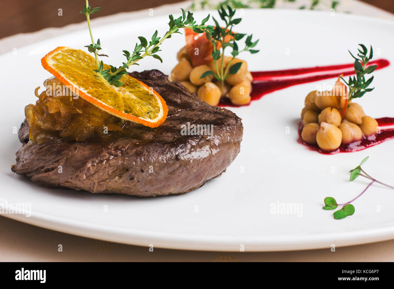Juicy beef steak with orange sauce with greens and chickpeas - Stock Image