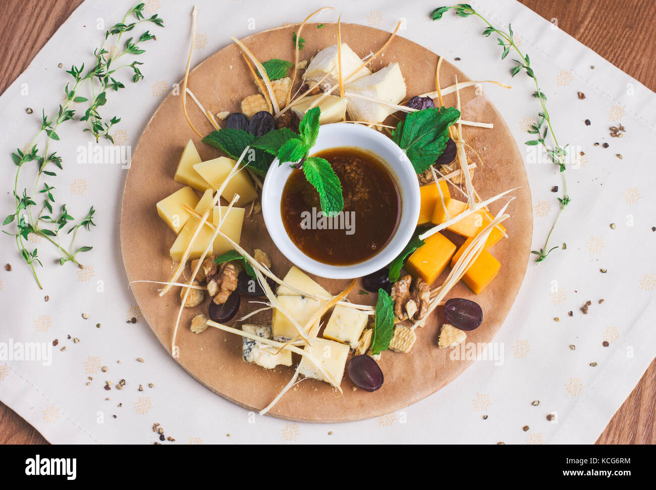 Different types of cheese with honey, nuts and fruits on round wooden Board - Stock Image