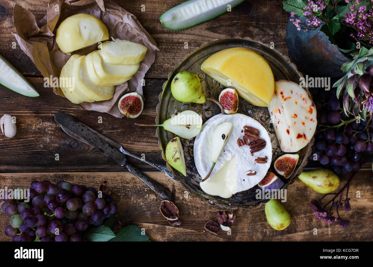The different cheese and fresh fruits on the wooden background - Stock Image