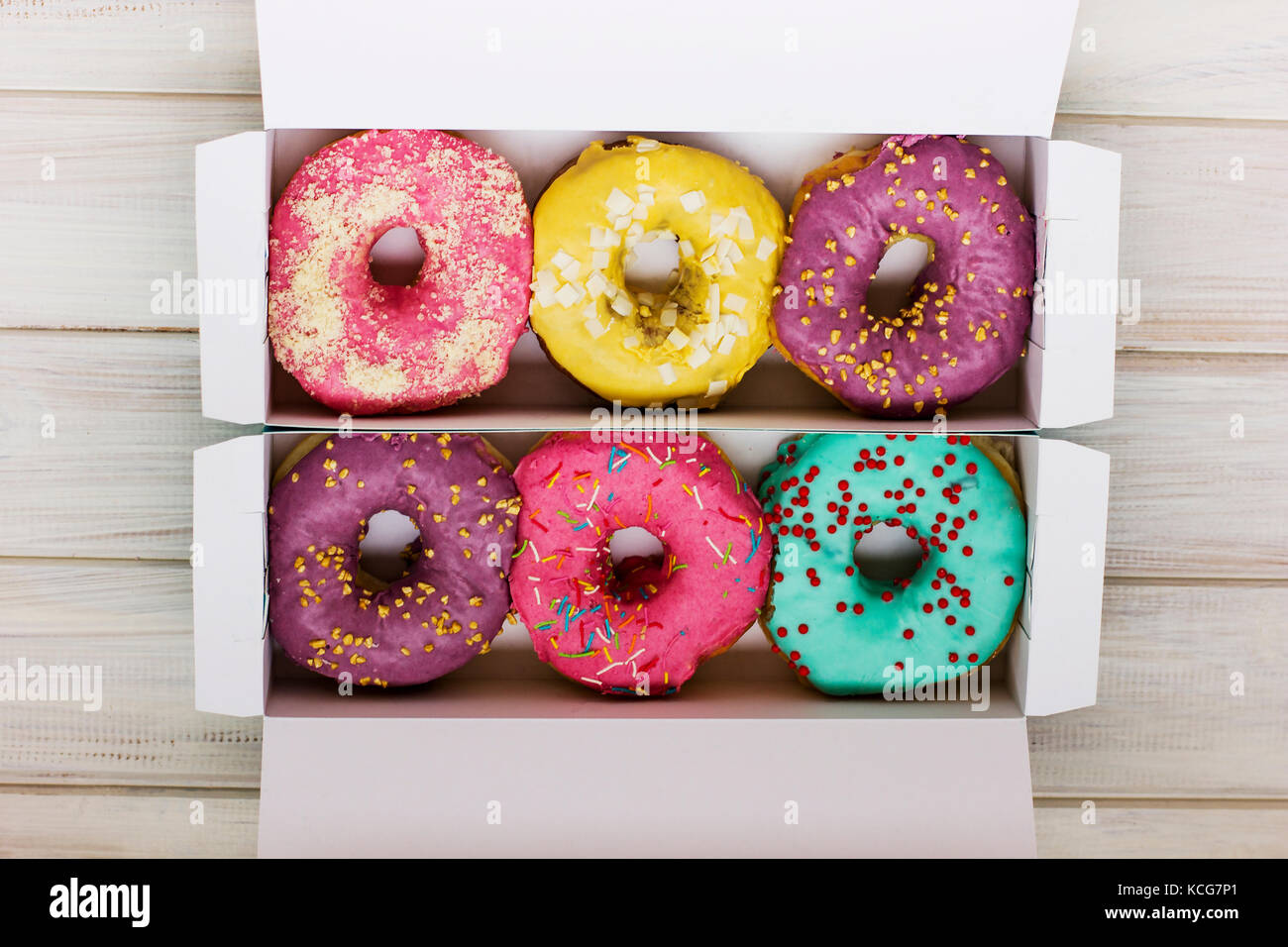 Colorful donuts in the cardboard box on the white wooden background - Stock Image