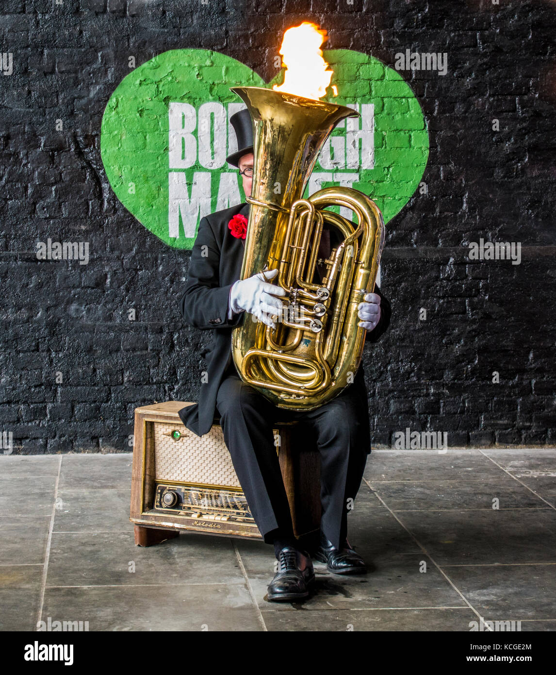 Man entertainer in a suit and top hat, sitting on an old gramophone, playing a tuba with a flame from the top. Borough - Stock Image