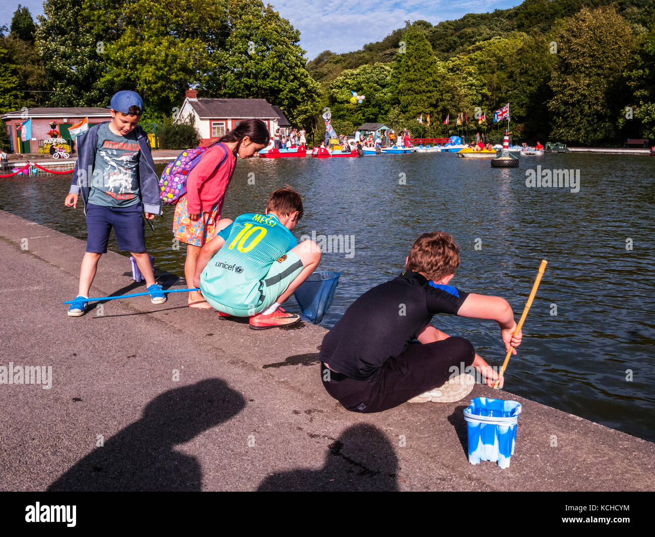 2 Boys fishing for newts in boating lake - Stock Image