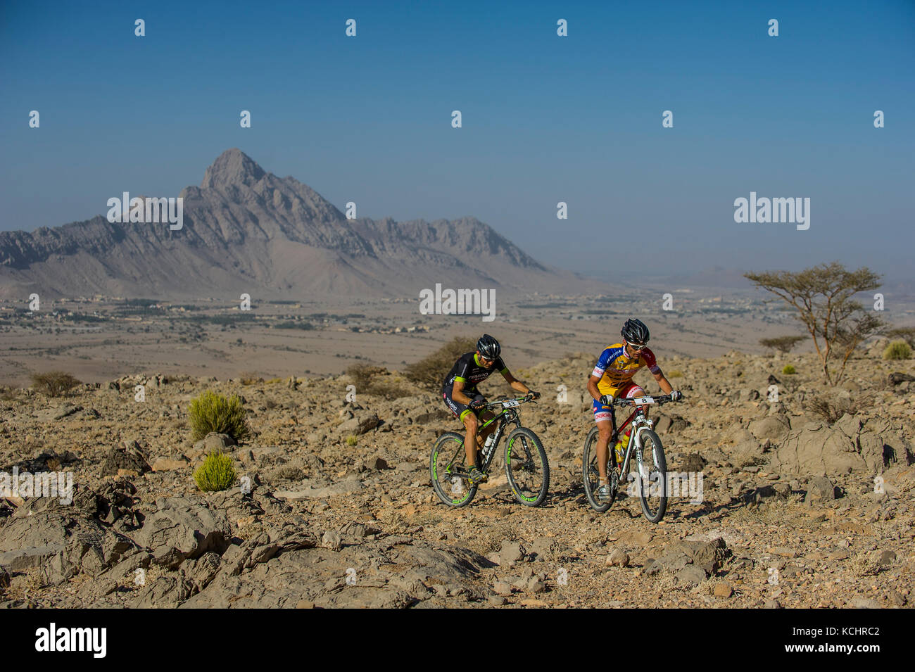 Competitors take part in the Trans Hajar mountain bike stage race in the Hajar mountains, Oman. - Stock Image