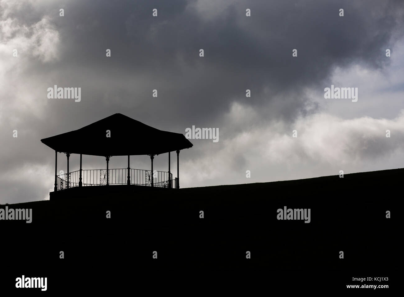 Silhouette of bandstand at top of hill against dark, moody clouds in sky - Stock Image
