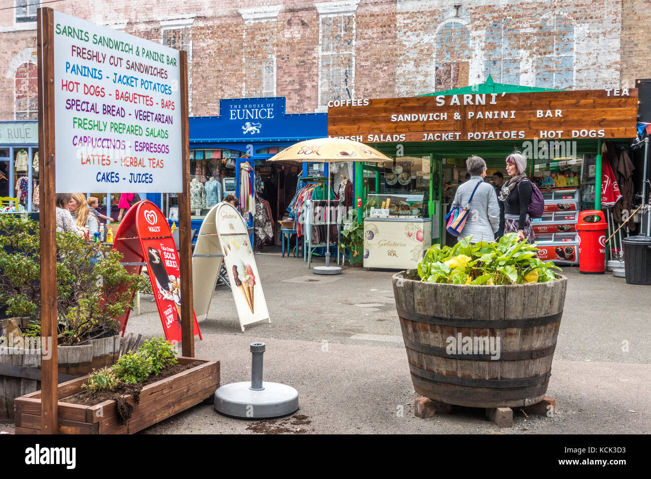 Two women friends chatting outside a food and drinks bar, among the various independent shops at Gabriel's Wharf, - Stock Image